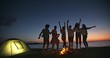 Six old multiethnic friends dncing on the beach near bonfire with drinks in hands, having a summer party, having fun 4k