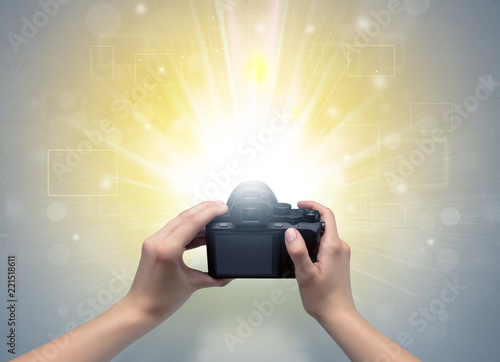 Obraz Naked hand taking picture with digital camera and glowing flash concept