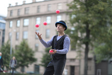 A Male Clown Juggles With Red Balls In The Town Square