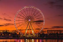 Illuminated Ferris Wheel With Colorful Sunset.