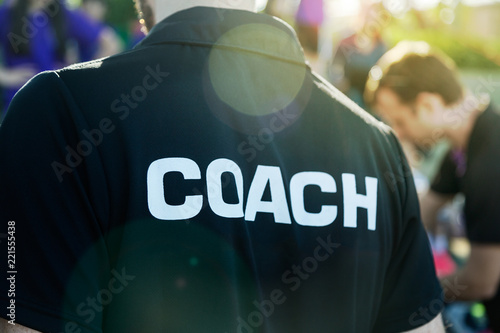Valokuvatapetti Sport coach in black shirt with white Coach text on the back standing outdoor at