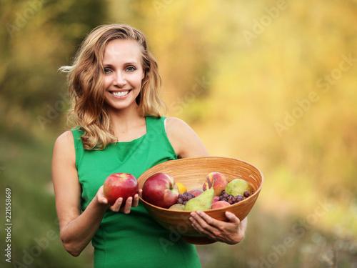 Fotografie, Obraz  Kobieta w zielonej sukience trzymająca miskę z owocami