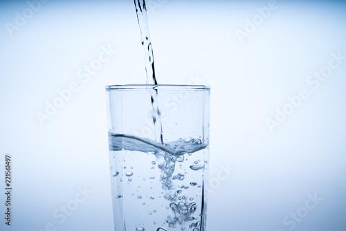 Papiers peints Eau Close up pouring drinking water into glass, studio shot
