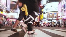 Amazing Low Angle Slow Motion Shot Of Crowd Walking Across The Street With Many Ads At Night On Times Square, New York.