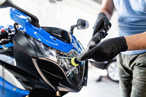 Motorcycle detailing - Man with orbital polisher in repair shop polishing motorcycle. Selective focus.