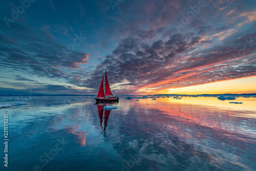 Greenland midnight Sunrise mirror panorama with red sail ship Fototapeta