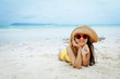 Portrait of a beautiful girl in sunglasses and bikini on the beach, she was sunbathing happy and relaxed by the sea.