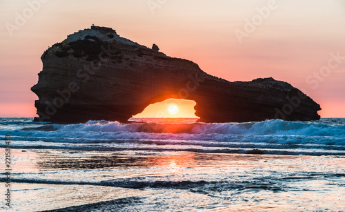 Sunset on a beach in Biarritz with the sun in the center of a rock's hole Canvas Print