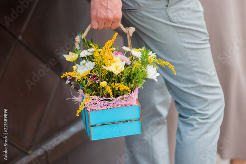 Foto op Canvas Bloemen The man is holding a floral composition