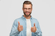 canvas print picture - Handsome young Caucasian bearded man does okay symbol, keeps thumb raised, approves good idea of companion, has cheerful expression, stands alone agaisnt white background. Body language concept