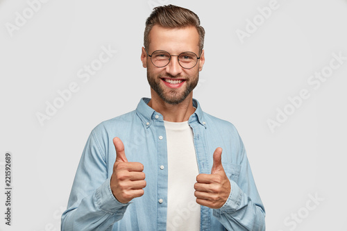 Fotografia  Handsome young Caucasian bearded man does okay symbol, keeps thumb raised, approves good idea of companion, has cheerful expression, stands alone agaisnt white background