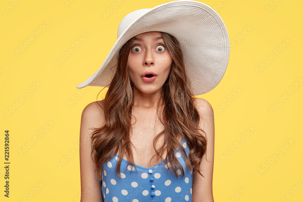 Fototapety, obrazy: Emotive surprised fashionable woman in summer hat, stares with bugged eyes, opens mouth from surprisement, dressed in polka dot clothes, stands against yellow background. Surprisement concept
