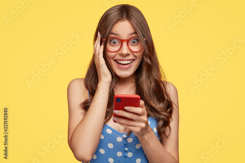 Fotografie, Obraz  Cheerful positive woman holds modern cell phone, forgets telephone number of boy