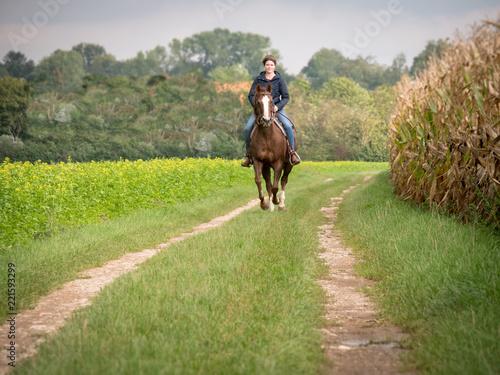 Obraz na plátně Junge Frau auf Pferd im Galopp