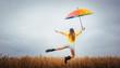 canvas print picture - Frau freut sich über den Regen und springt mit dem Regenschirm in die Luft