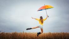 Frau Freut Sich über Den Regen Und Springt Mit Dem Regenschirm In Die Luft
