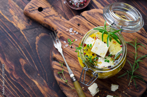 Feta cheese marinated in olive oil with fresh herbs in glass jar. Wooden background. Top view. Copy space.