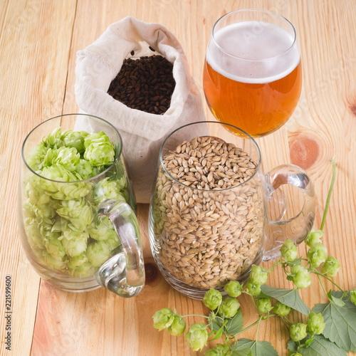 Photo Glass of beer, cones of hop, pale caramel malt in glass mugs and chocolate malt in bag, Ingredient in craft beer brewing from grain barley malt