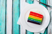 Rainbow Cake On A White Plate. Colorful Wooden Background. Top View. Copy Space.