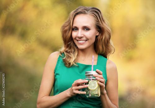 Fototapeta Kobieta w zielonej sukience trzymająca kubek z woda cytryną i mięta obraz