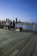 Three people sitting on bench at dusk at Gantry State Plaza Park on the East River waterfront in Long Island City, Queens, NY with Manhattan skyline in distance