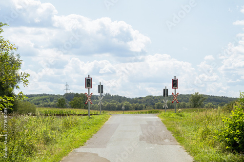 Valokuva  Empty level crossing without barriers,  rail crossing, view with blue sky and clouds, countryside
