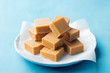 Fresh caramel fudge candies on a plate. Blue background. Close up.