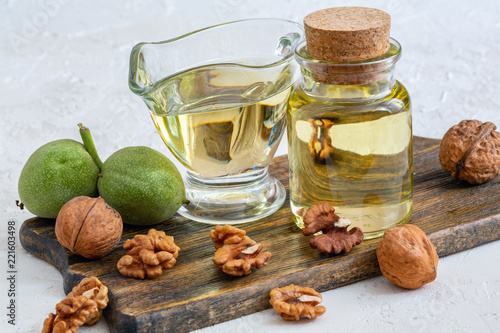 Keuken foto achterwand Kruiderij Walnut oil in a bottle and a glass cup.