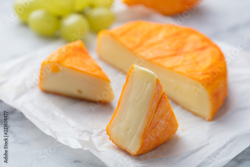 Cheese with washed orange rind. French or German. Marble table background. Close up.