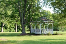A White Gazebo In The Garden Of The Park On A Summer Day.