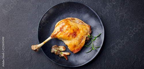 Duck leg confit with mushroom sauce on black plate. Slate background. Top view.