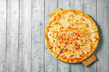 Top View Tasty Cheese Italian Pizza On Wooden Table