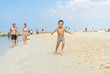 Happy little boy running on sand tropical beach. Positive human emotions, feelings, joy. Funny cute child making vacations and enjoying summer.