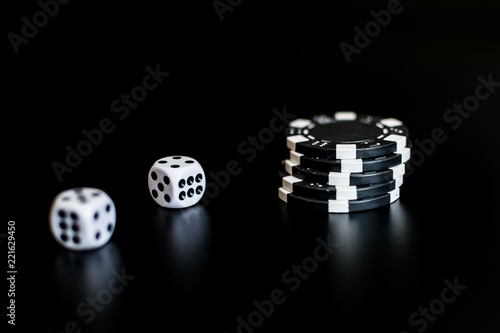 фотография  dice and monochrome casino chips on black background