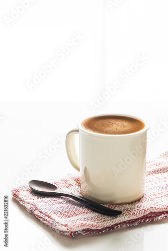 White cup of coffee on white table with bright