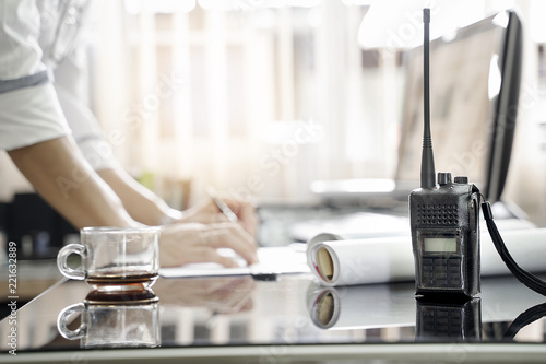 Two way radios on table with blur background of men working Tapéta, Fotótapéta