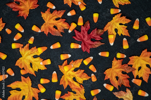 Foto op Plexiglas Herfst Candy corn and colorful maple leaves in an autumn scene over a black background