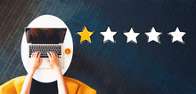 One Star Rating With Person Using A Laptop On A White Table