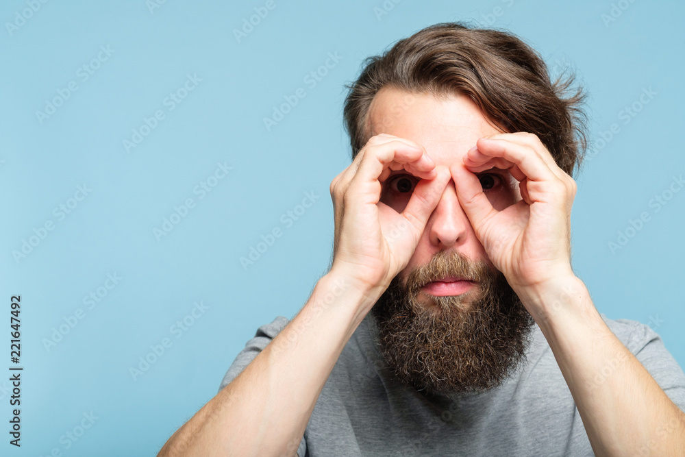 Fototapeta funny ludicrous joyful comic playful man pretending to look through binoculars made of hands. portrait of a young bearded guy on blue background. emotion facial expression concept