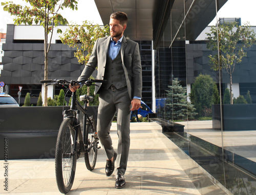 Photo  Confident young businessman walking with bicycle on the street in town