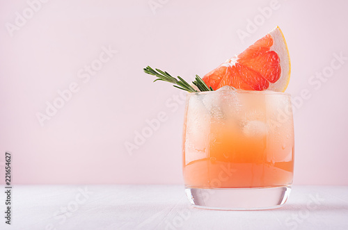 Cold fresh homemade grapefruit cocktail with ice, rosemary and pieces citrus on pastel pink background.