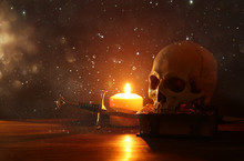 Human Skull, Old Book, Sword And Burning Candle Over Old Wooden Table And Dark Background.