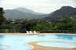 The outdoor swimming pool is in a natural setting with a mountain backdrop.