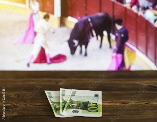 Money euro on the background of a TV on which show bullfight, sports betting, euro