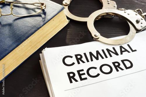 Fotografía  Criminal record and handcuffs on a desk.