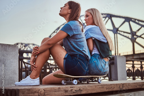 Foto op Aluminium Ontspanning Side view of a two young hipster girls sitting on a skateboard and looking away on background of the old bridge at sunset.
