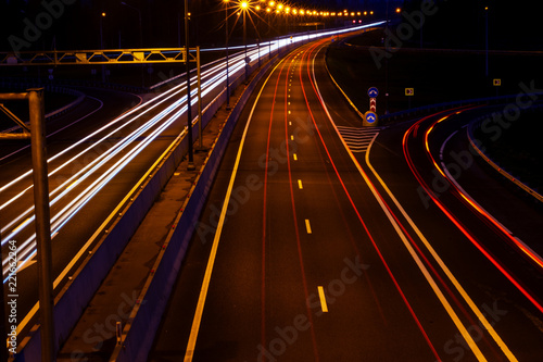 Spoed Foto op Canvas Nacht snelweg Cars light trails on a curved highway at night. Night traffic trails. Motion blur. Night city road with traffic headlight motion. Cityscape. Light up road by vehicle motion blur.