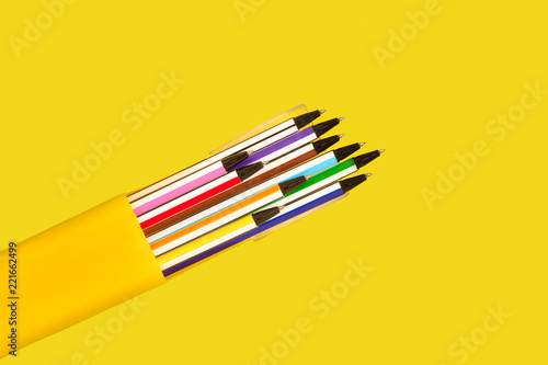 Valokuva  new bright colored pens lying in a box on a yellow background