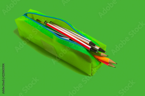 new bright colored pens and pencils lying in a pencil case on a green background Tapéta, Fotótapéta