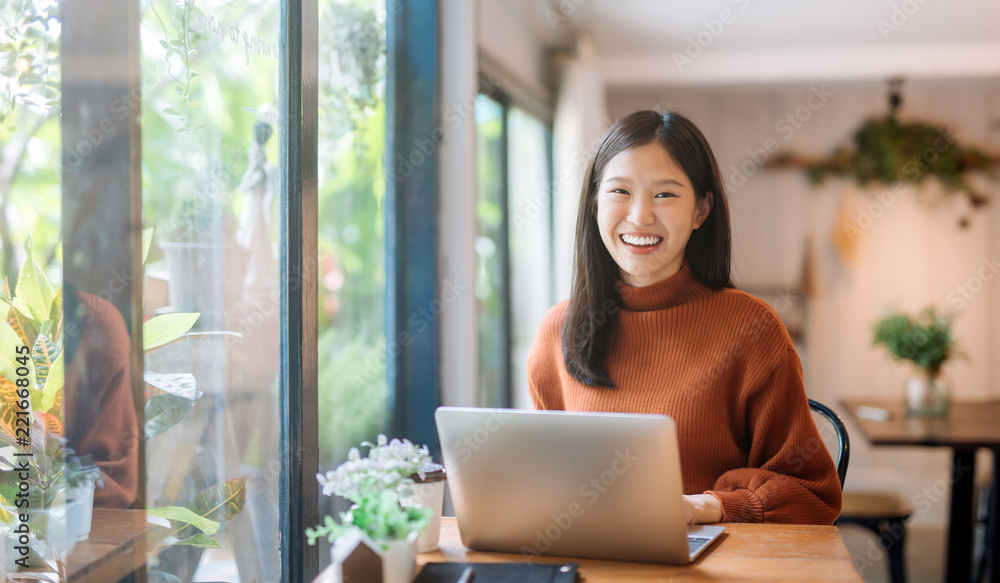 Fototapeta Happy young Asian girl working at a coffee shop with a laptop